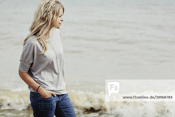 'Portrait of a young woman with long blond hair at the ocean; Hastings  Sussex  England'
