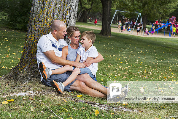 'A married couple spending quality time with their son in a park during a family outing; Edmonton  Alberta  Canada'
