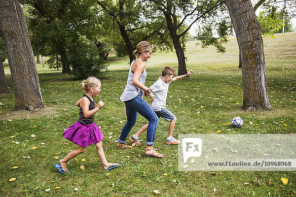 'A mother playing soccer with her kids in a park during a family outing; Edmonton  Alberta  Canada'
