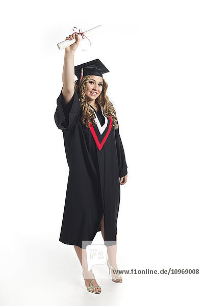 'Young woman graduate holding her diploma up in celebration of her graduation; Edmonton  Alberta  Canada'