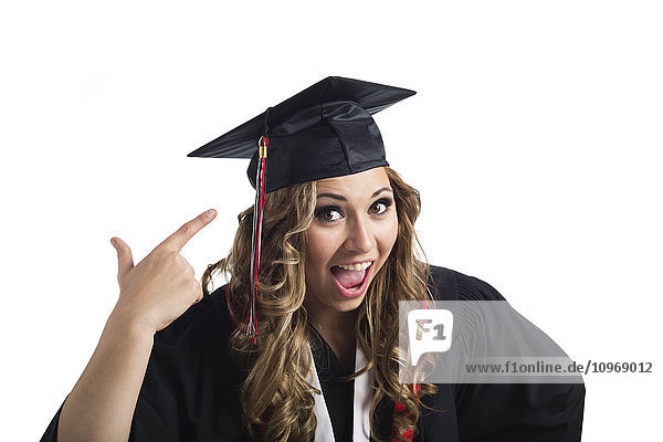 'Young graduating woman pointing at her grad cap in celebration; Edmonton  Alberta  Canada'