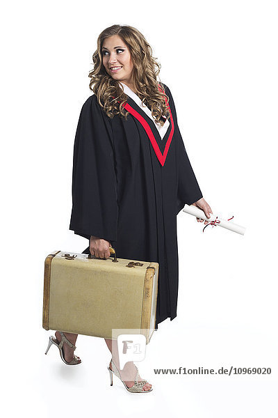'Young graduating woman holding luggage symbolizing that she is now leaving home; Edmonton  Alberta  Canada'