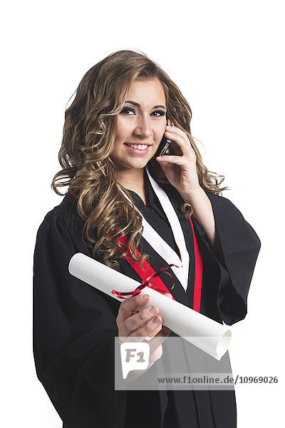 'Young graduating woman holding her diploma and talking on her smart phone; Edmonton  Alberta  Canada'