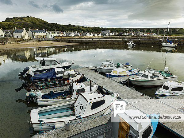 'Boats moored in the tranquil harbour of the North Sea with houses in the background; Cullen,  Moray,  Scotland'