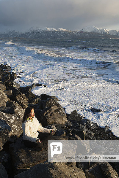 Woman practicing meditation on a rocky beach  Homer Spit  Southcentral Alaska