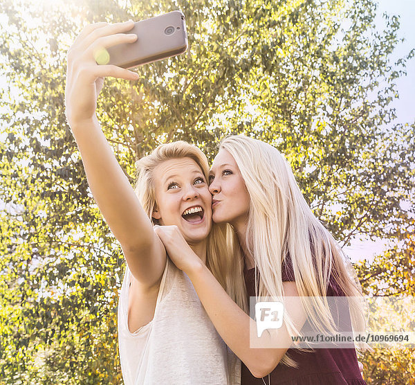 'Two sisters having fun outdoors in a city park in autumn and taking selfies of themselves with one sister kisses the other on the cheek; Edmonton  Alberta  Canada'