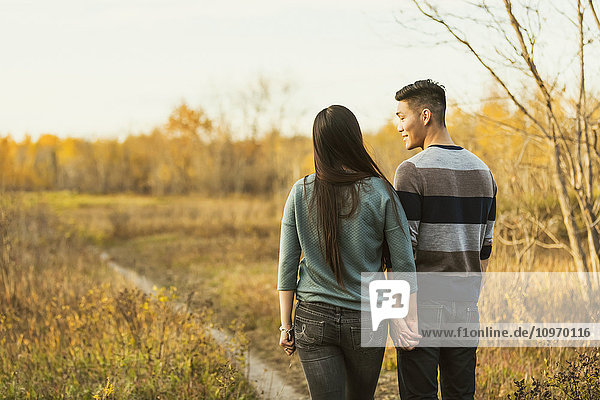 'A young Asian couple holding hands while walking in a park in autumn and and enjoying the warmth of the evening sunshine; Edmonton  Alberta  Canada'