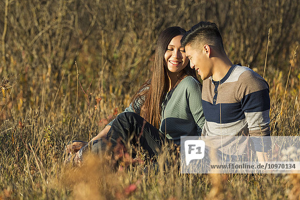 'A young Asian couple enjoying quality time together outdoors in a park in autumn in the warmth of the sunlight during the early evening; Edmonton  Alberta  Canada'