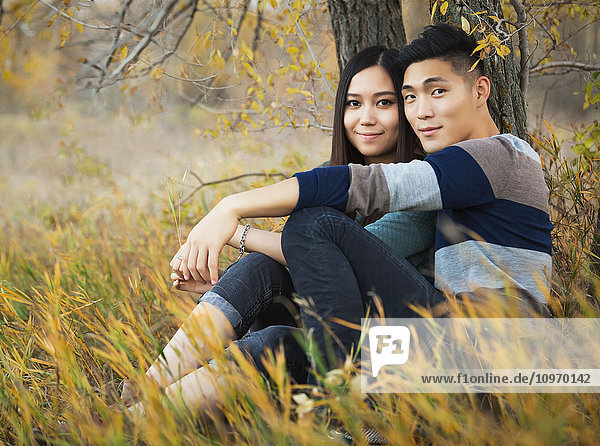 'A young Asian couple enjoying a romantic time together outdoors in a park in autumn sitting under a tree and posing for the camera; Edmonton  Alberta  Canada'