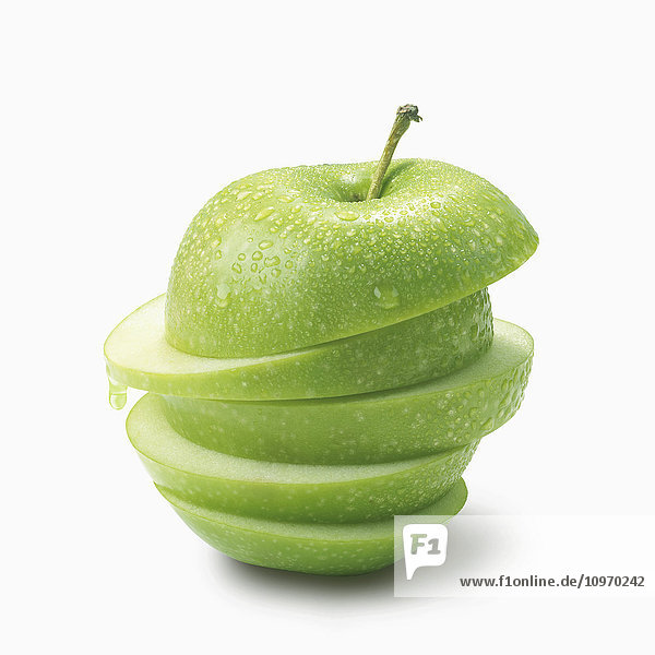 'A green apple cut into slices and piled on a white background; Toronto  Ontario  Canada'