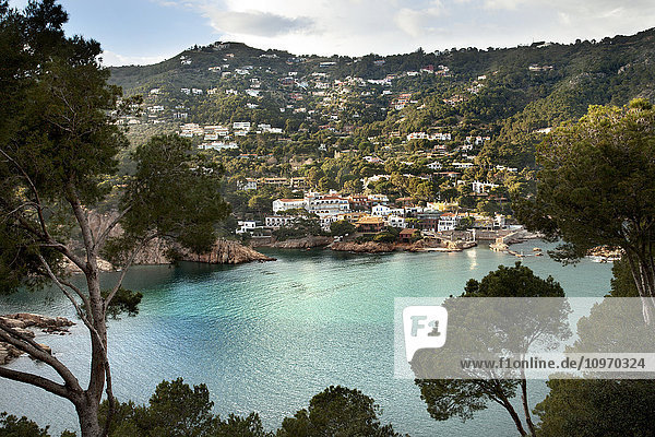 'Turquoise water in a lake with houses on a hillside; Gerone  Catalonia  Costa Brava  Spain'