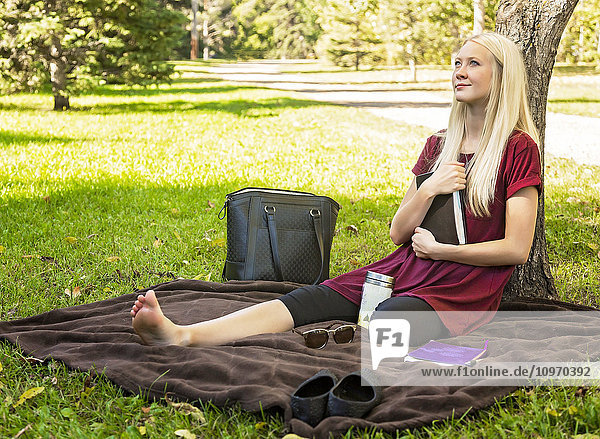 'A young woman holding her Bible close to her chest while spending personal devotional time outdoors in a park in autumn; Edmonton  Alberta  Canada'