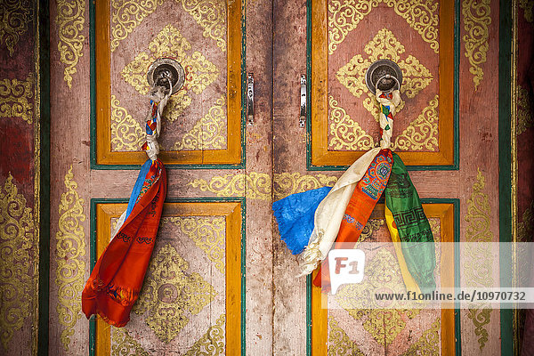 'Cloth is braided together to create a decorated door pull on the doors on a Tibetan style monastery; Ladakh  India'