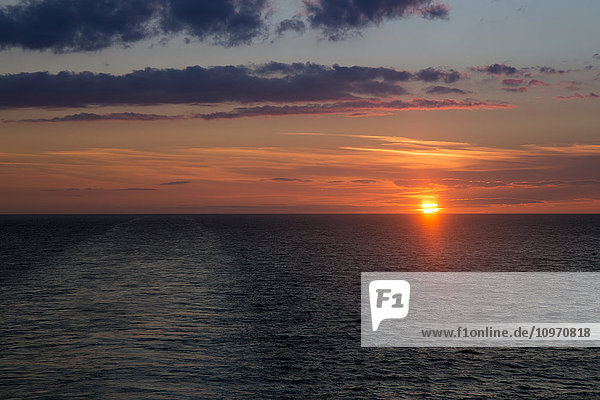 'A dramatic sky with glowing pink clouds as the sun sets over the North Sea; England'