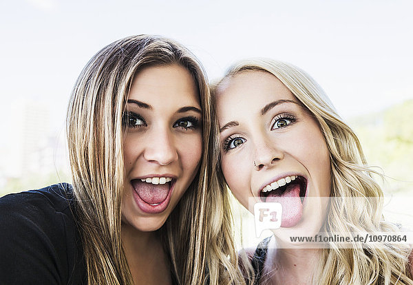 'Two girlfriends posing for the camera and making funny faces in a downtown city park; Edmonton  Alberta  Canada'