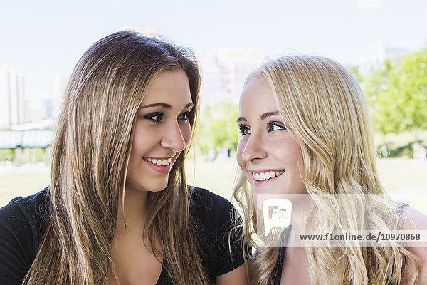 'Two girlfriends looking at each other and smiling while enjoying the outdoors in a downtown city park; Edmonton  Alberta  Canada'