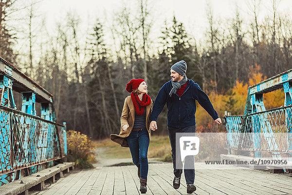 'A young couple running on a bridge during the autumn season in a city park; Edmonton  Alberta  Canada'