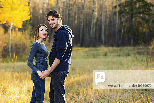 'A young couple walking and stopping to pose for the camera in a city park in autumn; Edmonton  Alberta  Canada'
