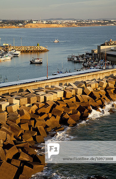 'Blocks of rock piled against a wall in the harbour  near Conil de la Frontera; Andalusia  Spain'