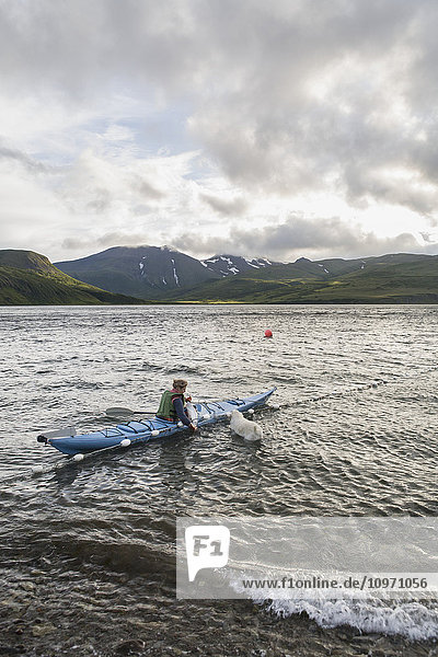'A Woman Tending Her Subsistence Salmon Net By Kayak At A Summer Fish Camp On The East End Of Unimak Island On The Edge Of Isanotski Strait; False Pass  Southwest Alaska  United States Of America'