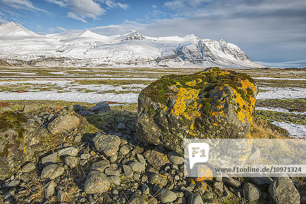 'Moss Covered Rocks And Snow Covered Mountains Along The Southern Coast; Iceland'