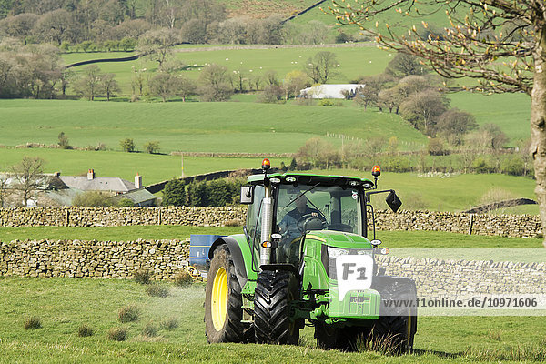 John Deere 6126r spreading fertilizer on upland pasture; Lancashire  England