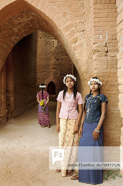 'Girls with flower garland and face paint standing against a wall; Bagan  Myanmar'