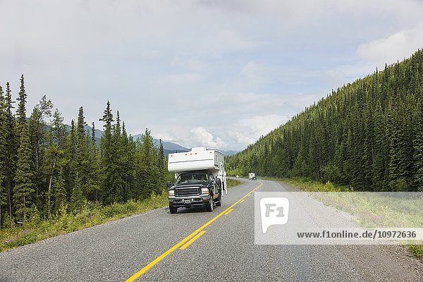 Truck and RV camper drive down the Alaska Highway  west of Fort Nelson  British Columbia  Canada  Summer