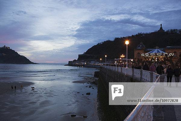 'People strolling on the promenade of Passeo de La Concha at dusk  looking towards Mount Urgull with the bay of La Concha to the left; San Sebastian  Spain'