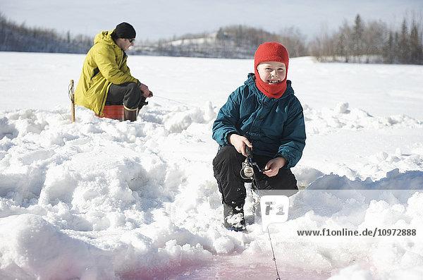 Boy ice fishing on Matanuska Lake in the Matanuska Valley north of Anchorage  Southcentral Alaska