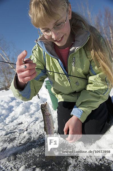 Girl ice fishing on Matanuska Lake in the Matanuska Valley north of Anchorage  Southcentral Alaska