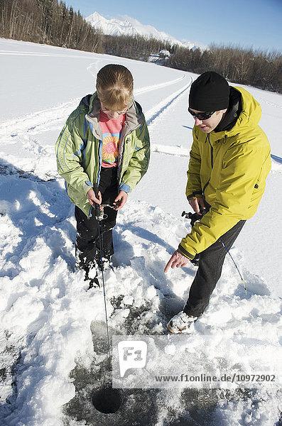 Girl ice fishing with a guide on Matanuska Lake in the Matanuska Valley north of Anchorage  Southcentral Alaska