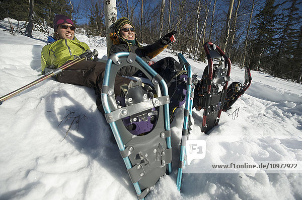 Snowshoers take a break in the sun while snowshoeing in Interior Alaska north of Fairbanks  winter
