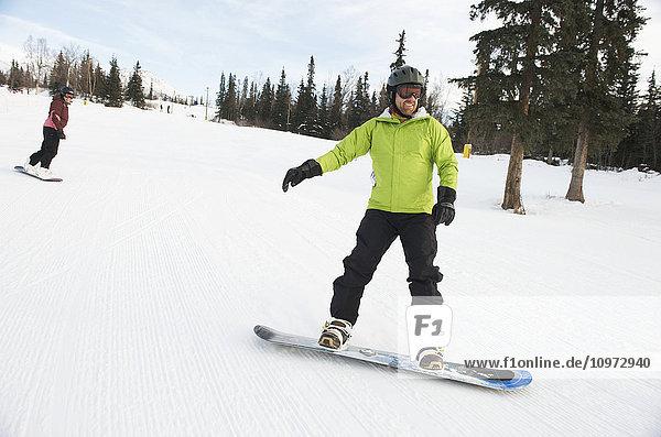 Couple snowboarding at Hilltop Ski Area in Anchorage  Alaska