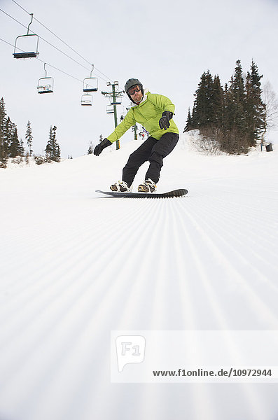 Man snowboards at Hilltop Ski Area in Anchorage  Alaska
