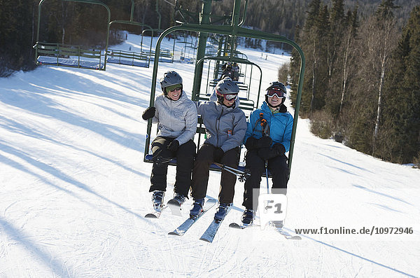 Three woman ride the chair lift at Hilltop Ski Area in Anchorage  Alaska