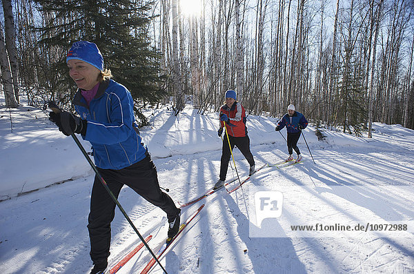 Friends enjoy nordic skiing on the Jim Whisenhant Cross Country Ski Trail system at Birch Hill Recreation Area in Fairbanks Alaska