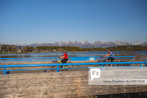 Bicyclist on the Tony Knowels Coastal Trail near Westchester Lagoon in Anchorage  Alaska  Spring.