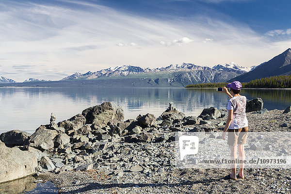 A woman takes a photo of Kluane Lake with a smart phone  Yukon Territory  Canada  Summer.