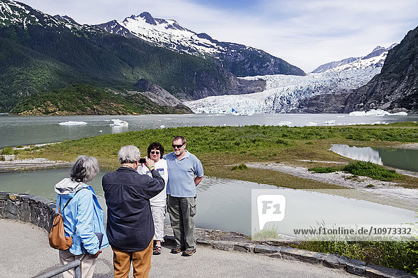 Tourists photographing Mendenhall Glacier and tourists in Tongass National Forest  Southeast Alaska