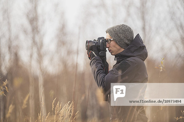 Photographer with camera raised and standing in a field  Alaska  Autumn