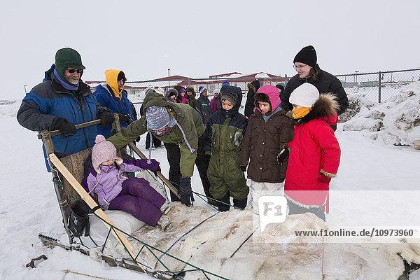 'Elementary school kids wearing winter gear wait to ride a sled around the lagoon  Barrow  North Slope  Arctic Alaska  USA  Winter'