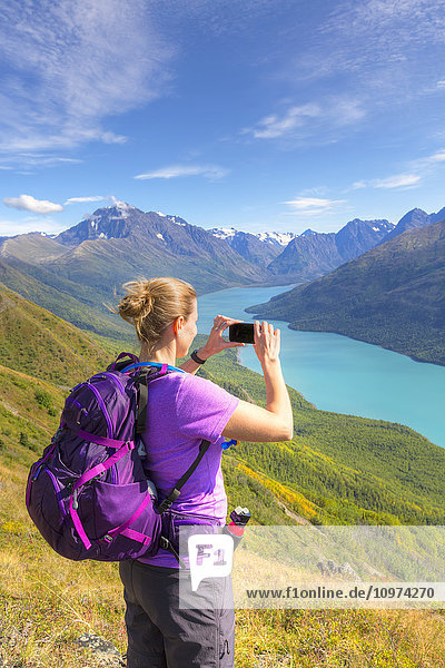 'Female hiker using a smartphone to photograph Eklutna Lake and the Chugach Mountains from the Twin Peaks Trail  Chugach State Park  Southcentral Alaska  Summer'