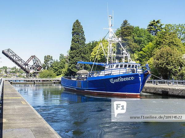 A fishing boat floats in a lock with a raised draw bridge in the background  Ballard Locks  Seattle  Washington  USA  Summer