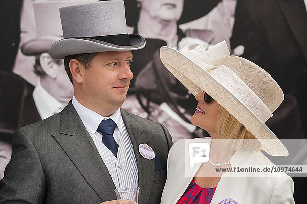 'A man in grey morning dress with a top hat  blue tie and matching handkerchief and wearing a badge for the Royal Enclosure at Ascot is looking shocked at his wife  who is smiling back at him. The portrait shows their heads and shoulders turned towards each other against the background of a poster on the wall showing men in top hats and morning dress; Ascot  England'