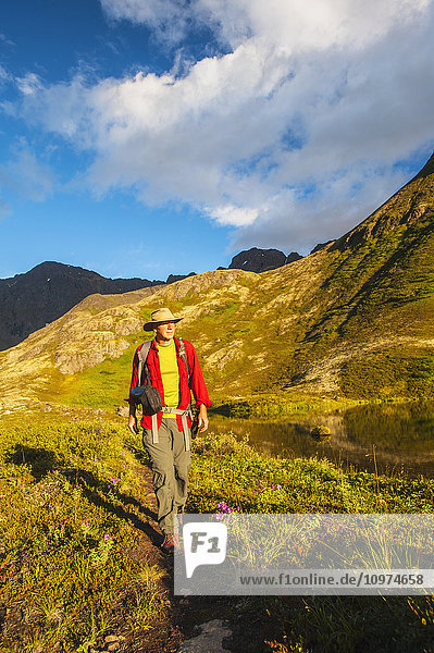 A man Hiking in Hanging Valley in South Fork near Eagle River on a summer day in South Central Alaska.