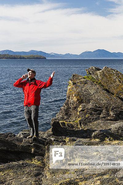 Man talks on his smart phone along the rocky shores of Tongass Narrows  Ketchikan  Southeast Alaska  Spring