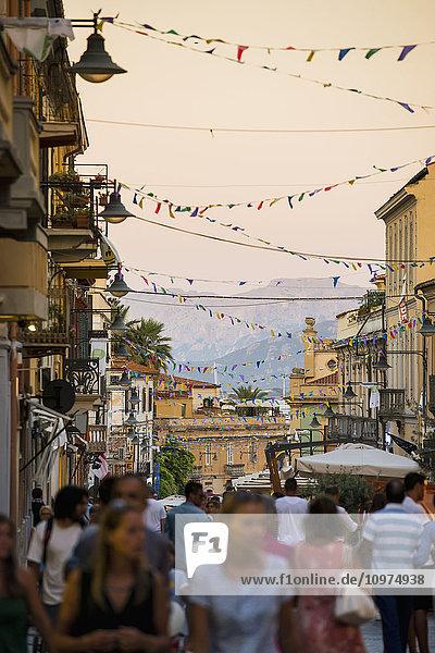 'Tourists walking down a busy street at dusk; Olbia  Sardinia  Italy'