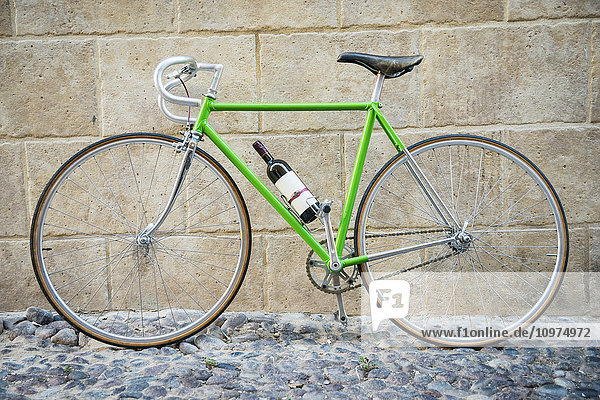 'Green bicycle with bottle of wine; Alghero  Sardinia  Italy'