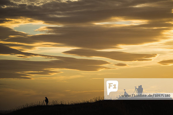 'Photographers at dawn photographing the sunrise; Iceland'